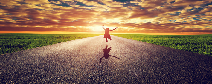 Happy woman jumping on long straight road, way towards sunset su
