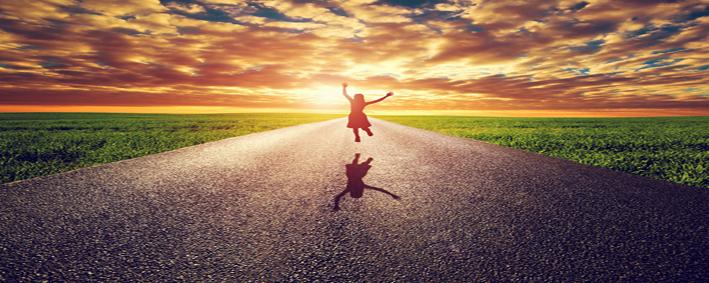 Happy woman jumping on long straight road, way towards sunset su