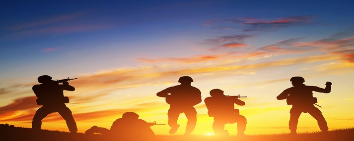 Soldiers in assault shooting with weapon, rifle at sunset. War, army, military.